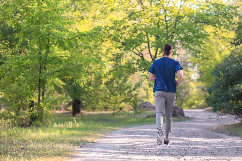Sportieve jonge mens die in park lopen stock fotografie