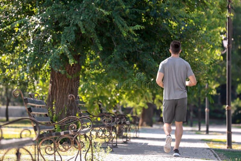 Sportieve jonge mens die in park lopen royalty-vrije stock afbeelding