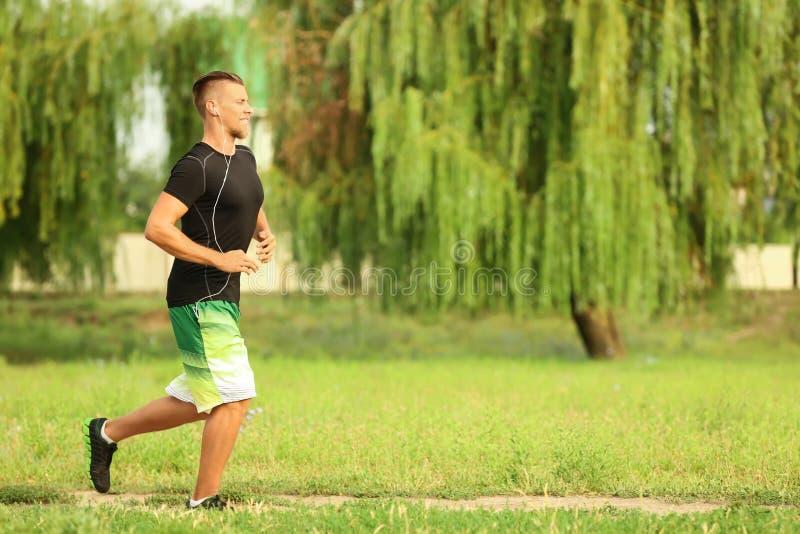 Sportieve jonge mens die in park lopen royalty-vrije stock foto's