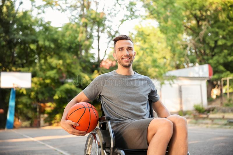 Sportieve jonge mens met balzitting in rolstoel in openlucht stock fotografie