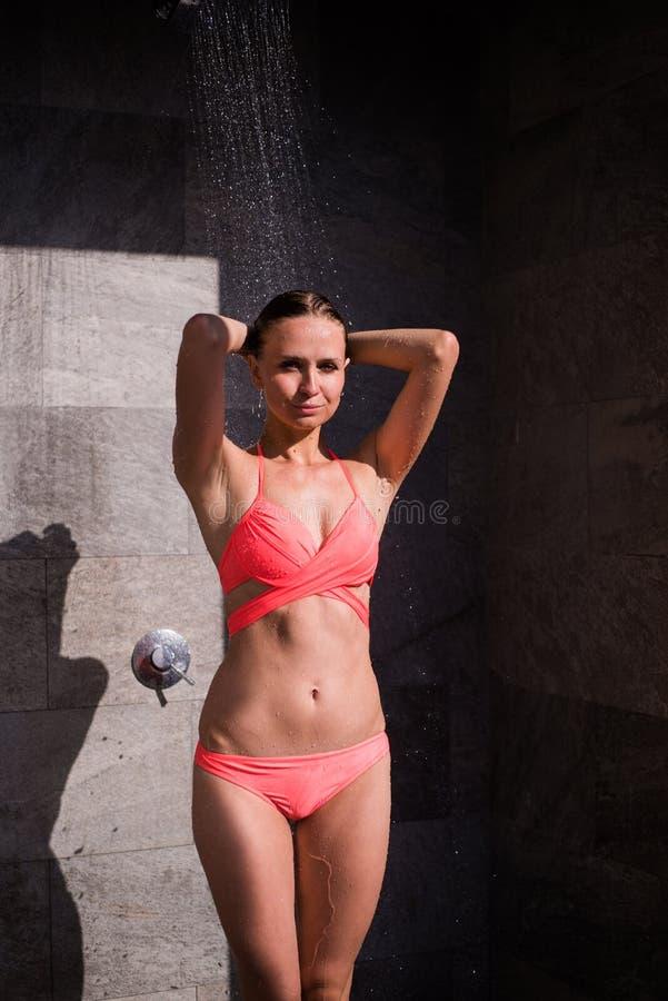 Sportieve jonge mooie sexy vrouw in een rood zwempak die verfrissende douche na het zwemmen in de openluchtpool nemen openlucht royalty-vrije stock afbeeldingen