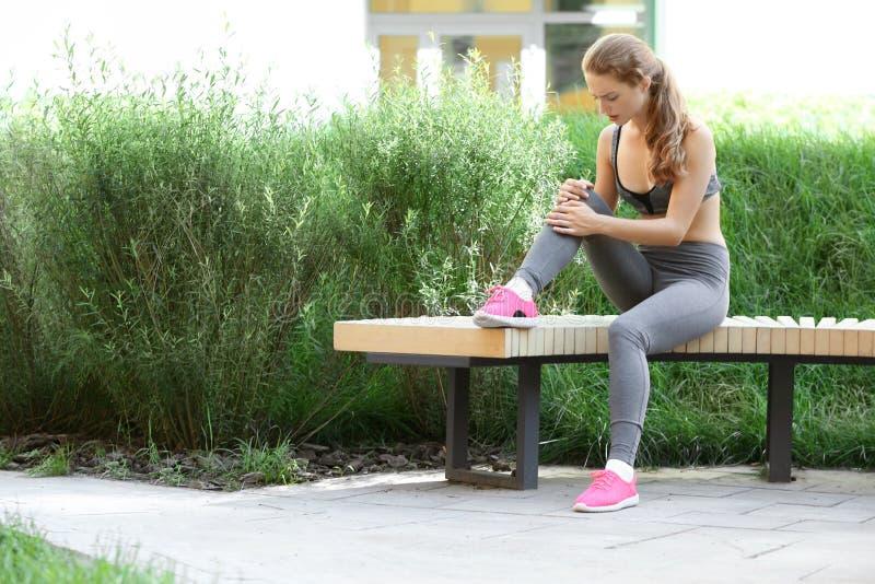 Sportieve jonge vrouw die aan kniepijn lijden terwijl het zitten op houten bank in park royalty-vrije stock foto