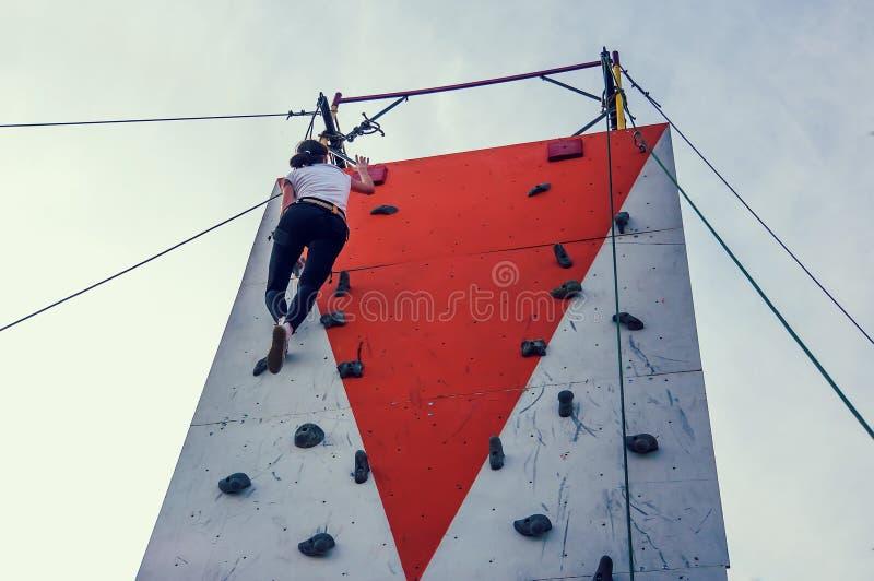Sportieve jonge vrouw die in een kleurrijke het beklimmen gymnastiek uitoefenen stock foto