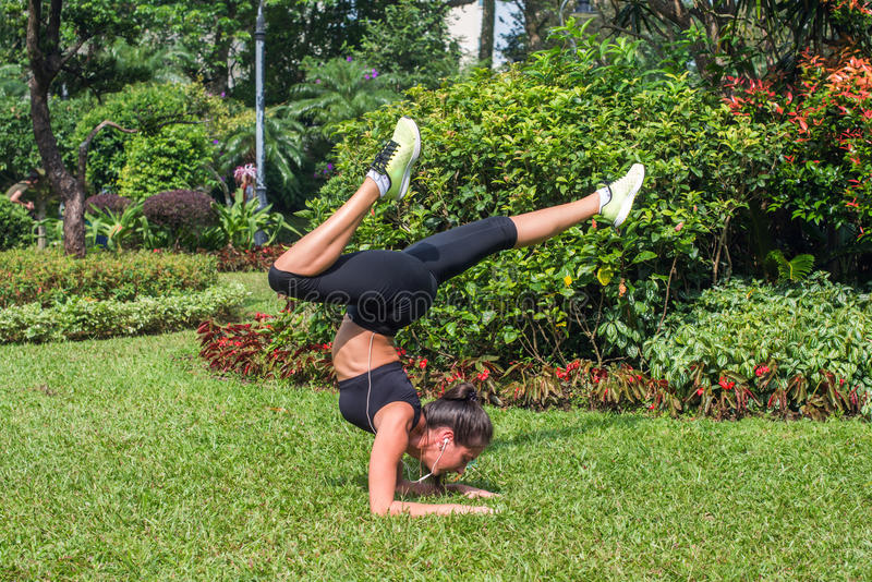 Sportieve jonge vrouw die handstandoefening met het buigen van benen op gras in park doen Geschikte meisje het praktizeren yoga i stock afbeeldingen