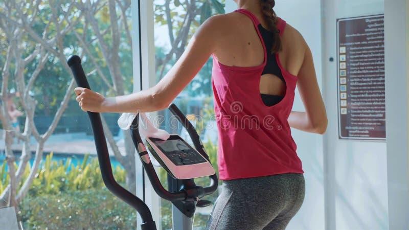 Sportieve jonge vrouw die op stapmachine bij de flatgebouw met koopflatsgymnastiek uitoefenen stock afbeelding