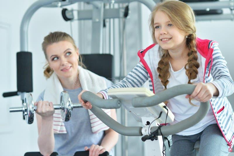 Sportieve jonge vrouw opleiding met tienerdochter stock afbeelding