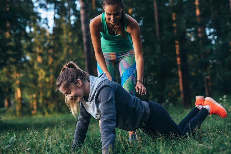 Sportieve jonge vrouwelijke trainer die een meisje tonen hoe te om knieopdrukoefeningen te doen terwijl opleiding in openlucht in royalty-vrije stock afbeeldingen