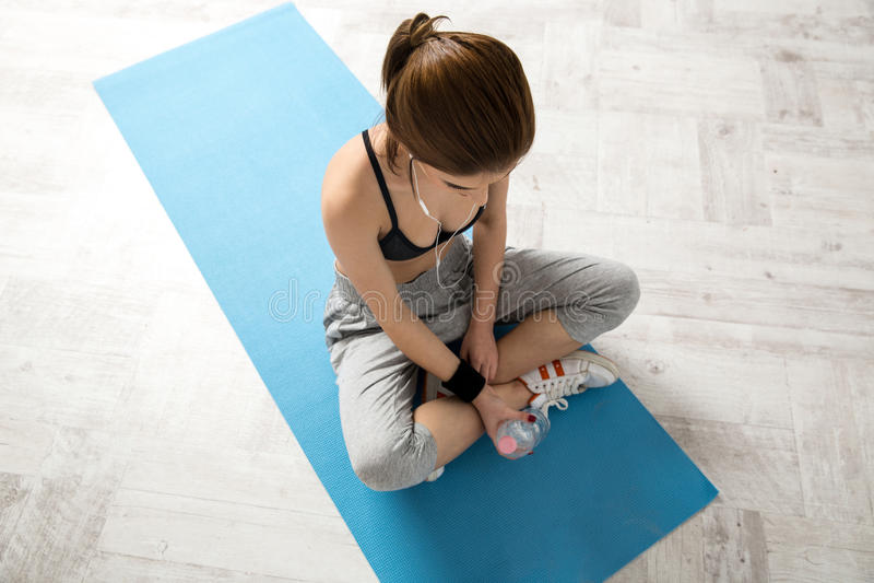 Sportieve jonge vrouwenzitting op de yogamat stock foto
