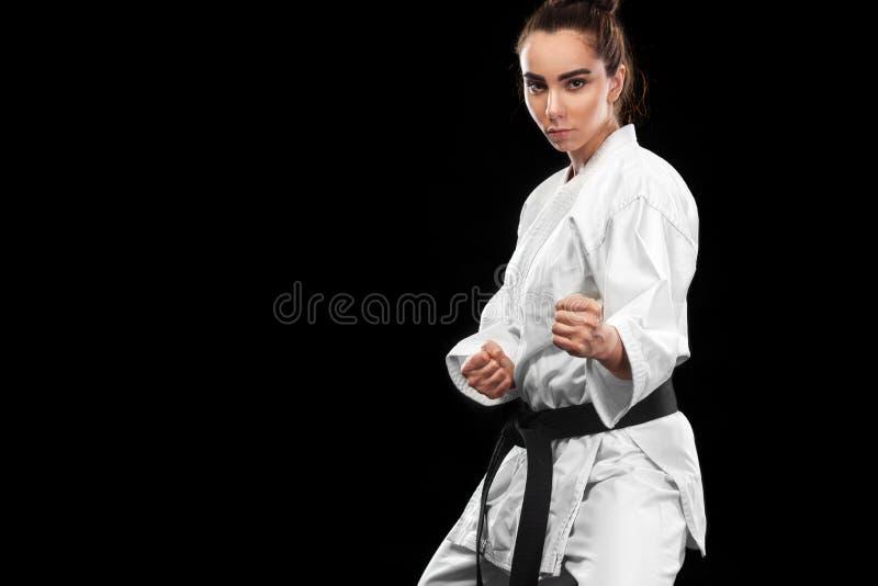 Sportieve karate en taekwondovrouw in witte kimono met zwart band op donkere achtergrond Sportconcept met exemplaarruimte royalty-vrije stock afbeelding