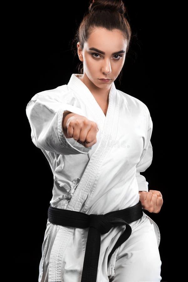Sportieve karate en taekwondovrouw in witte kimono met zwart band op donkere achtergrond Sportconcept met exemplaarruimte stock afbeeldingen