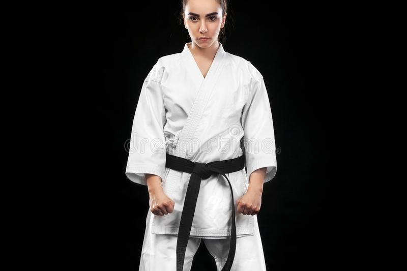 Sportieve karate en taekwondovrouw in witte kimono met zwart band op donkere achtergrond Sportconcept met exemplaarruimte royalty-vrije stock fotografie
