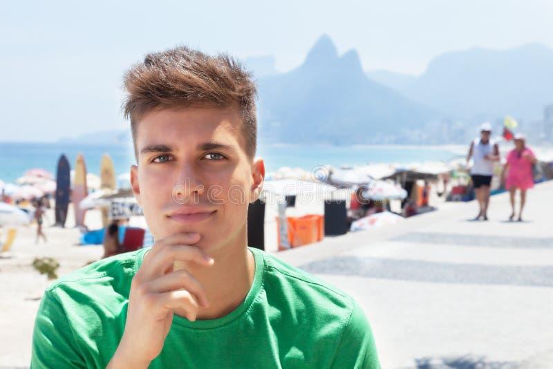 Sportieve kerel in een groen overhemd bij strand in Brazilië stock foto's
