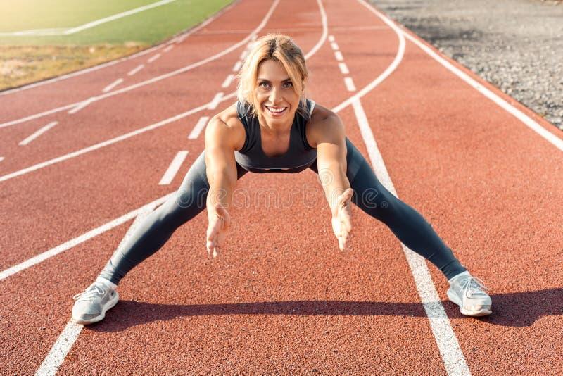Sportieve levensstijl De jonge vrouw op stadionbenen die zich opzij bij spoor het buigen uitrekken overhandigt vooruit opgewekt g royalty-vrije stock foto
