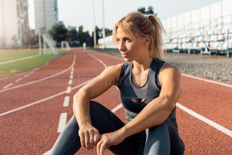 Sportieve levensstijl Jonge vrouw die op stadionzitting op spoor opzij dreamful close-up kijken stock afbeeldingen