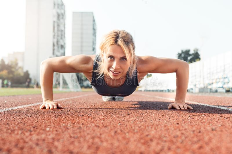 Sportieve levensstijl Jonge vrouw op stadion die duw UPS doen die gelukkig vooraanzicht glimlachen stock afbeeldingen