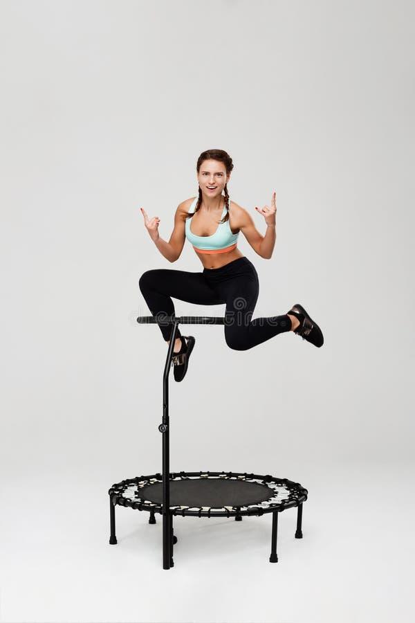 Sportieve meisje opleiding op rebounder en showig rotsteken stock foto's