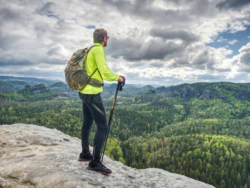 Sportieve mens bij berg het piek kijken op bergvallei royalty-vrije stock foto