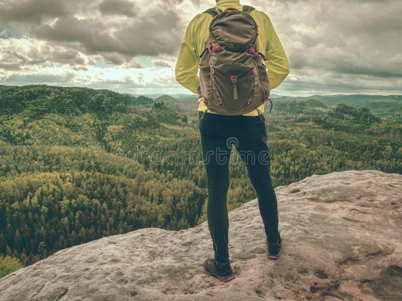 Sportieve mens bij berg het piek kijken op bergvallei royalty-vrije stock afbeelding
