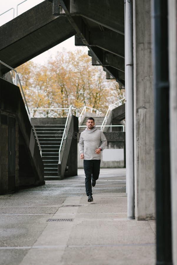 Sportieve mens die in de herfst lopen stock afbeeldingen
