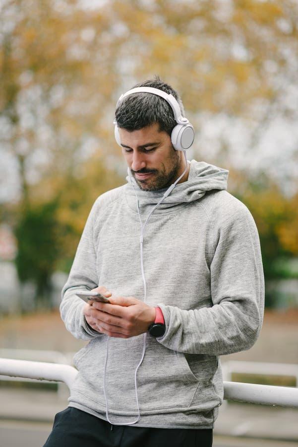 Sportieve mens die een opleidingsrust voor het gebruiken van smartphone nemen stock afbeeldingen