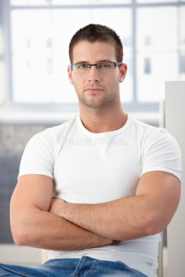 Sportieve mens die glazen draagt die gekruiste wapens zitten stock afbeeldingen