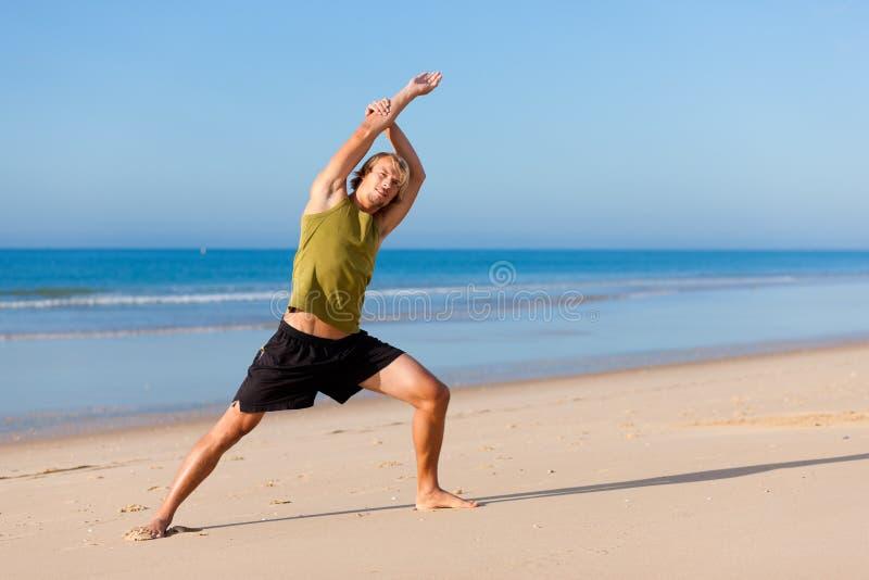 Sportieve mens die gymnastiek op het strand doet royalty-vrije stock afbeeldingen