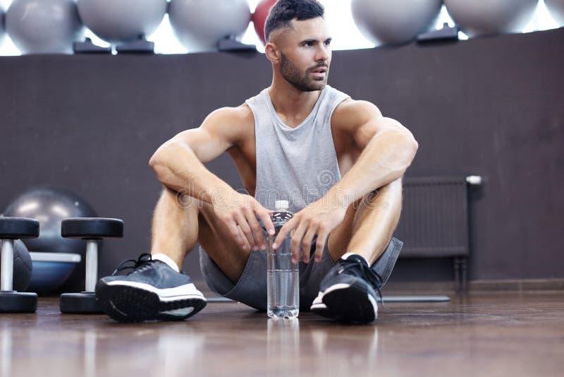 Sportieve mens die, hebbend onderbrekings drinkwater na het doen van oefening rusten stock afbeeldingen
