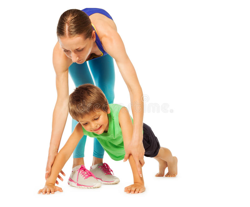 Sportieve moeder die haar zoon helpen die het duwen UPS doen stock afbeeldingen