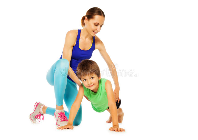 Sportieve moeder die haar zoon onderwijzen die het duwen UPS doen stock afbeelding