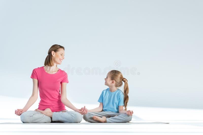 Sportieve moeder en dochter het praktizeren lotusbloempositie met gyan mudraasana op wit royalty-vrije stock foto's