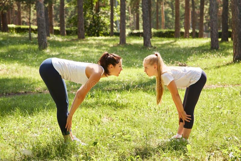 Sportieve moeder en dochter vrouw en kind opleiding in een park sporten en fitness familie stock foto's