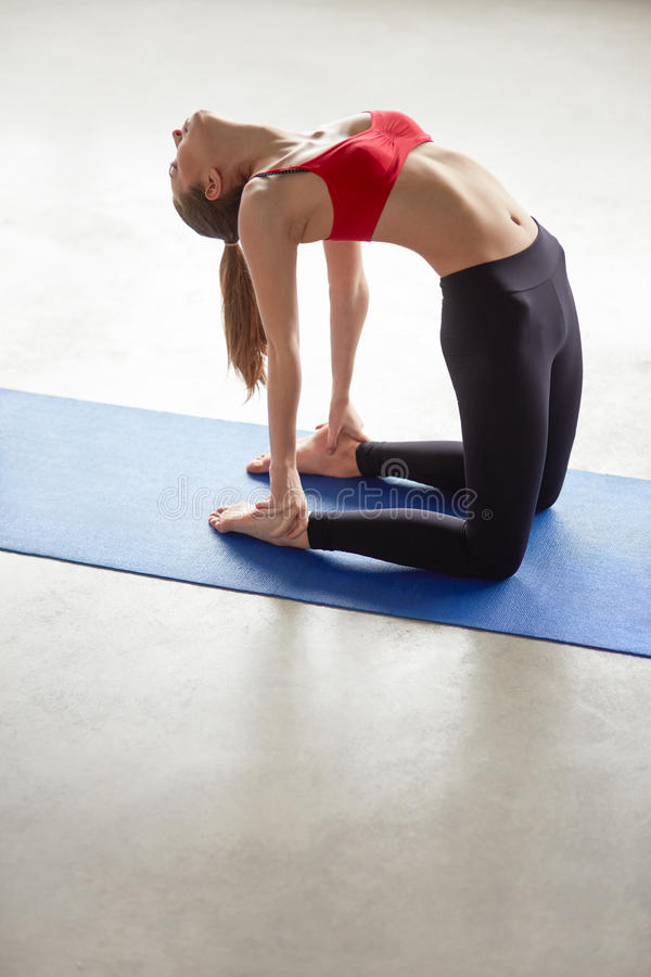 Sportieve mooie jonge vrouw het praktizeren yoga stock afbeelding