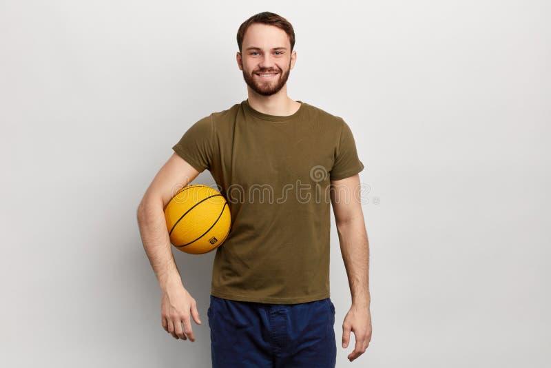 Sportieve positieve atleet met een bal die de camera bekijken royalty-vrije stock fotografie