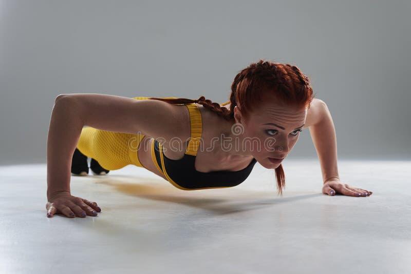 Sportieve ruwe vrouw die opdrukoefeningen doen stock foto's
