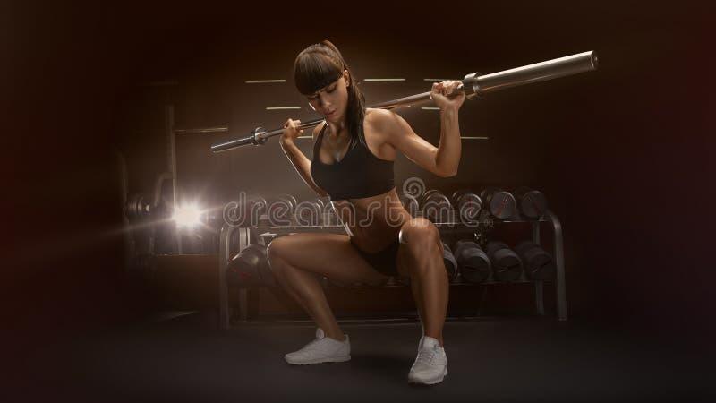 Sportieve sexy vrouw die hurkende training in gymnastiek doen royalty-vrije stock afbeelding