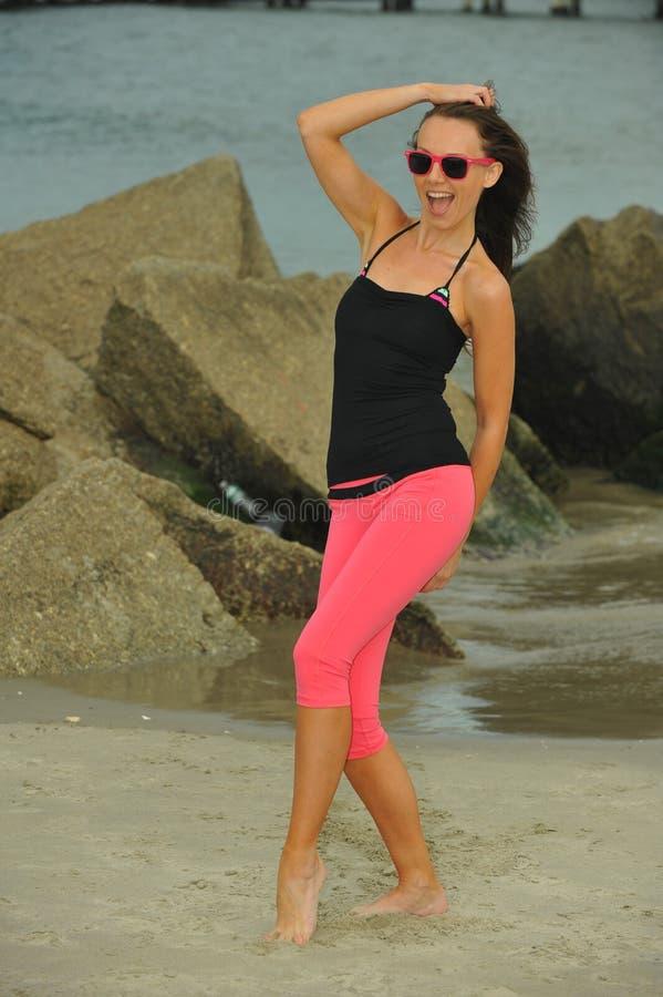 Sportieve slanke vrouw in roze beenkappen en zonnebril die bij het strand stellen royalty-vrije stock foto