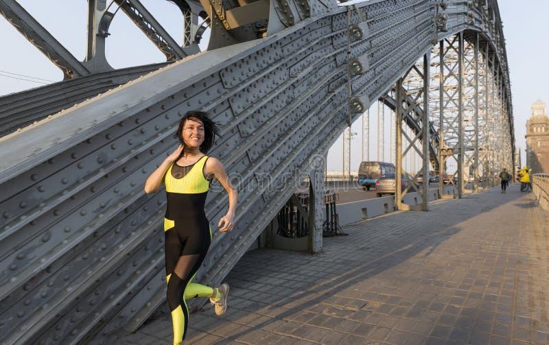 Sportieve slanke witte meisjeslooppas over de metaal brug en het glimlachen stock fotografie