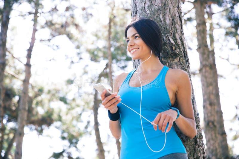 Sportieve smartphone van de vrouwenholding met hoofdtelefoons in openlucht stock foto