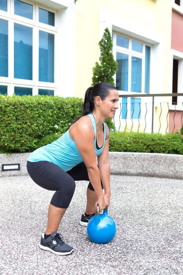 sportieve Spaanse vrouw in blauwe opleiding met kettlebell die dode lift doen royalty-vrije stock foto's