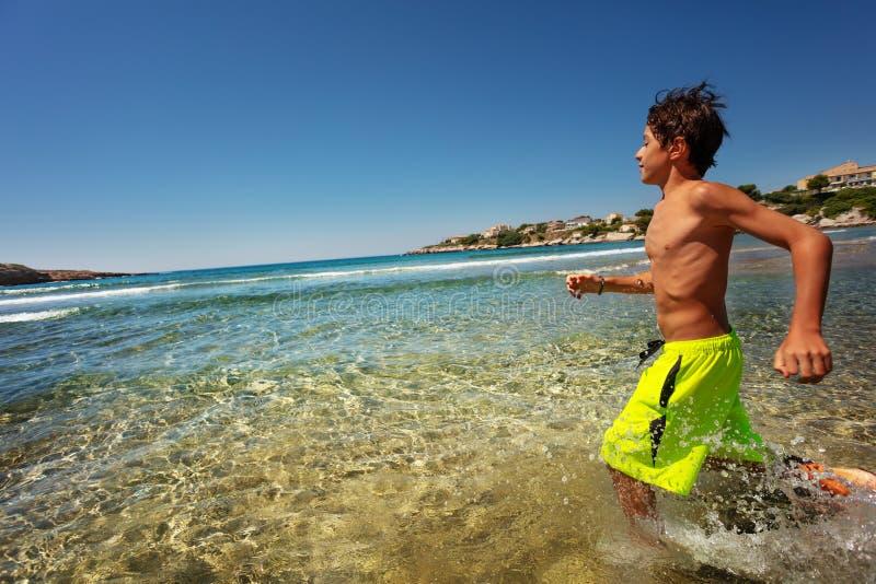 Sportieve tiener die in ondiep zeewater lopen royalty-vrije stock foto's