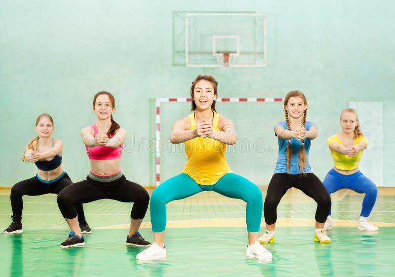 Sportieve tieners die hurkzit in schoolgymnastiek maken royalty-vrije stock foto