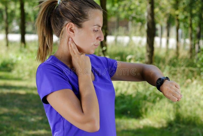 Sportieve vrolijke vrouw die harttarief meten tijdens de rust van de geschiktheidstraining royalty-vrije stock afbeeldingen