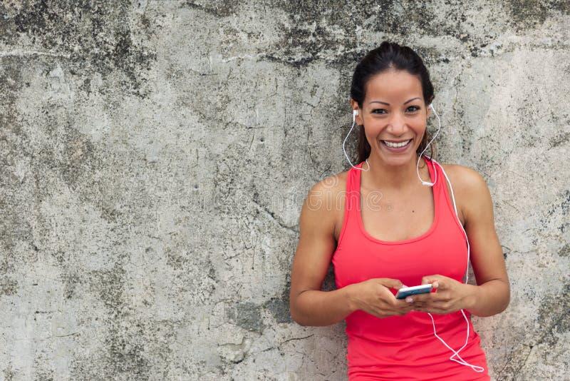 Sportieve vrolijke vrouw die smartphone gebruikt stock fotografie