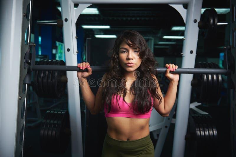 Sportieve vrouw die barbell opheffen stock foto