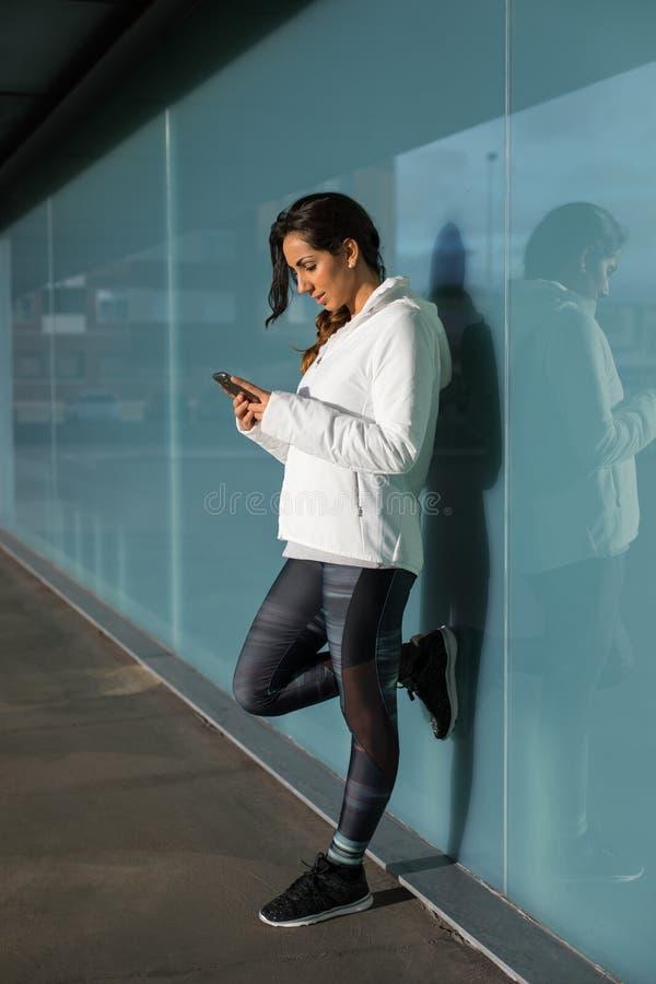 Sportieve vrouw die celtelefoon met behulp van tijdens trainingrust royalty-vrije stock foto's