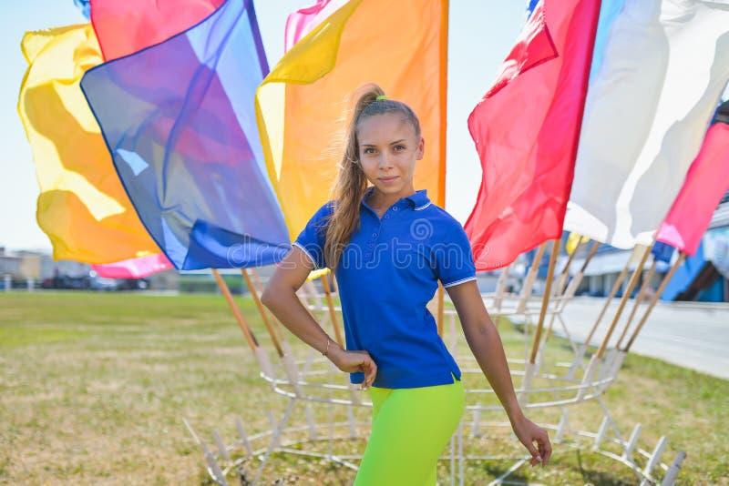 Sportieve vrouw die en bij stadion, kleurrijke vlaggen op achtergrond stellen glimlachen stock fotografie