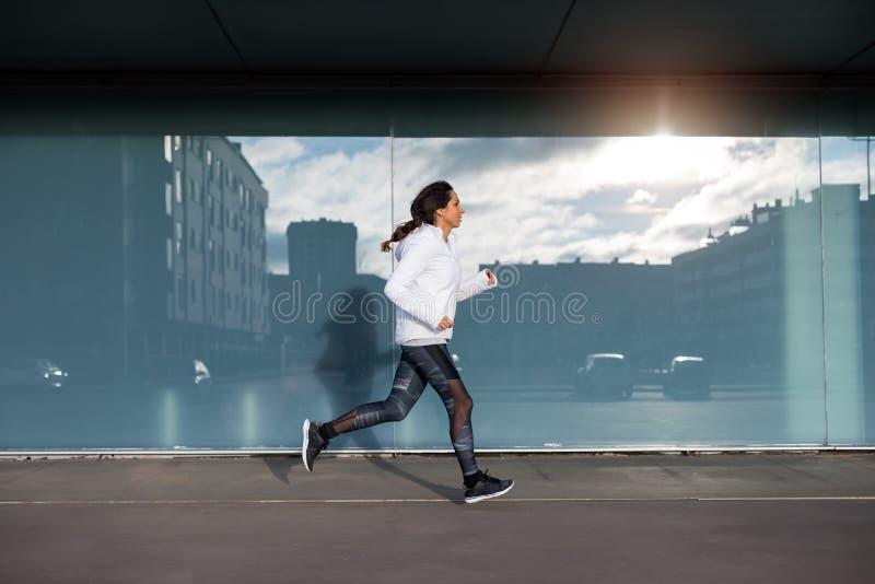 Sportieve vrouw die en in de stad lopen uitoefenen stock afbeelding