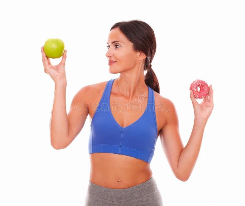 Sportieve vrouw die geschiktheid over suikerachtig voedsel kiezen royalty-vrije stock afbeelding