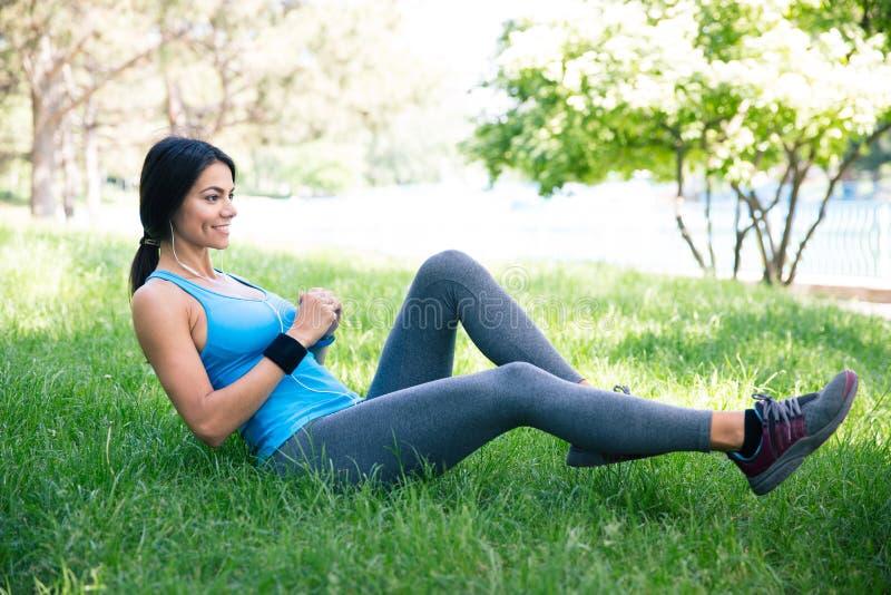 Sportieve vrouw die het uitrekken exercsises in park doen zich stock foto