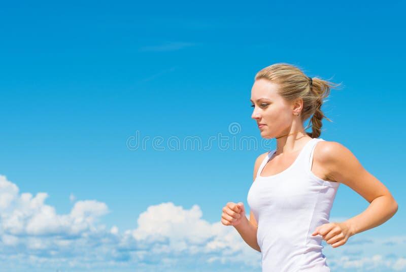 Sportieve vrouw die langs het strand lopen stock fotografie